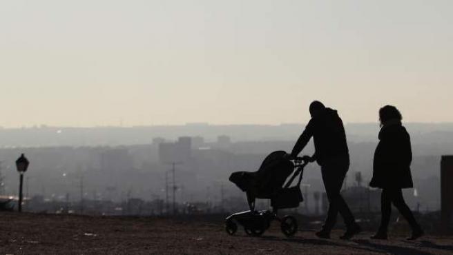 Imagen de una familia paseando bajo la contaminación en el Cerro del Tío Pío (Vallecas).