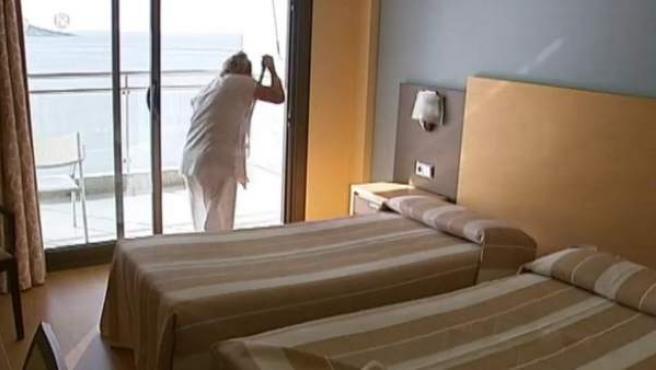 Una mujer limpia una habitación en un hotel de la costa.