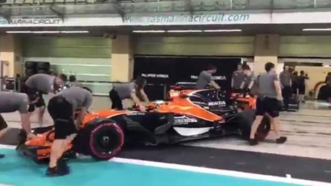 Mecánicos de McLaren empujan el coche de Alonso en los test de Abu Dabi.