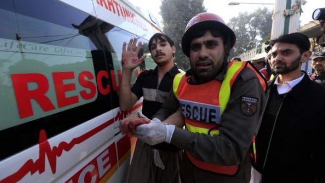 Un miembro de los servicios de rescate ayuda a un herido tras un ataque terrorista perpetrado en la Universidad de Peshawar, en Pakistán.