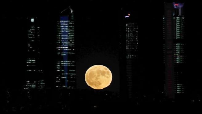 """Vista de la superluna entre los rascacielos del complejo empresarial """"Cuatro Torres Business Area"""" de Madrid."""