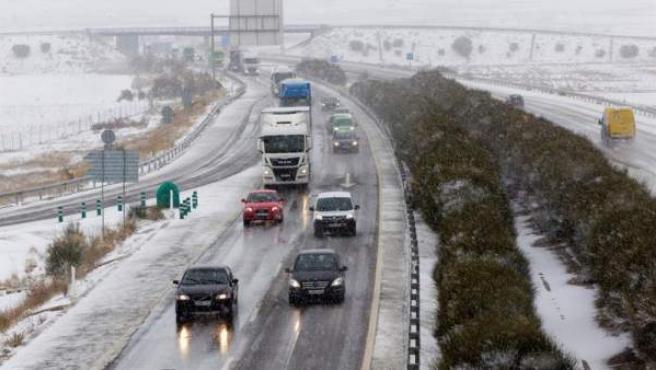 Varios vehículos transitan entre la nieve por la autovía A-23 a su paso por Santa Eulalia del Campo.