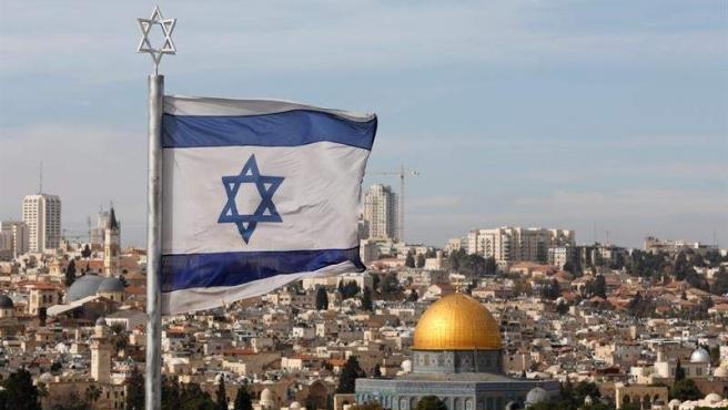 Una bandera israelí ondea en el antiguo cementerio judío del Monte de los Olivos, en la ciudad vieja de Jerusalén.