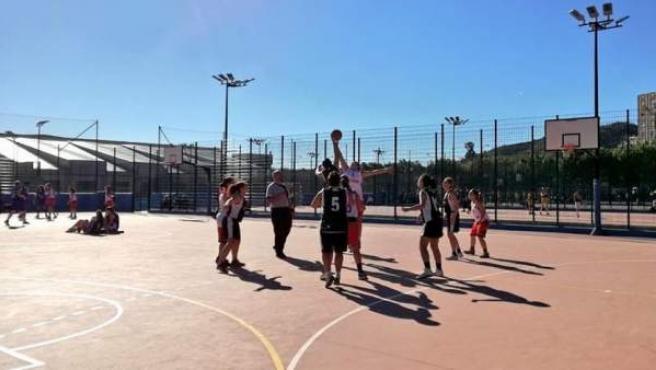 Un grupo de niños juega al baloncesto.