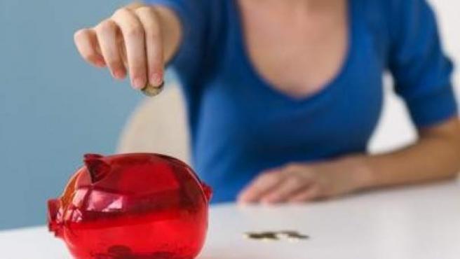 Una joven pone dinero en una hucha, en una imagen de archivo.