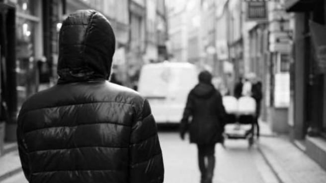 Un hombre persigue a una mujer por la calle.