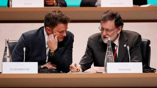 El presidente del Gobierno español, Mariano Rajoy, y su homólogo luxemburgués, Xavier Bettel, durante la sesión plenaria de la cumbre del clima celebrada en la isla de Seguin, en el oeste de París (Francia).