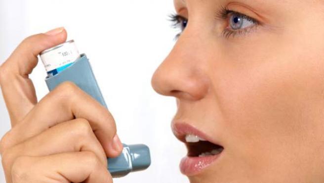Una mujer usando un dilatador de las vías respiratorias.