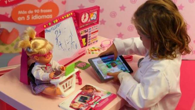 Una niña jugando un una tablet y una muñeca.