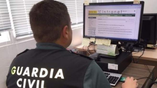 Imagen de un agente e la Guardia Civil delante de un ordenador.