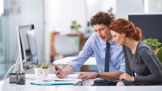 Dos compañeros de trabajo conversan en la oficina.