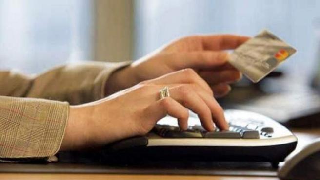 Una mujer utilizando su tarjeta de crédito para comprar por Internet.