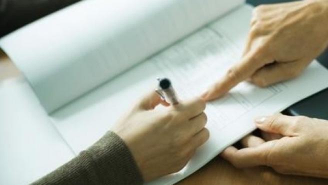 Una mujer señala con un dedo donde firmar un contrato.