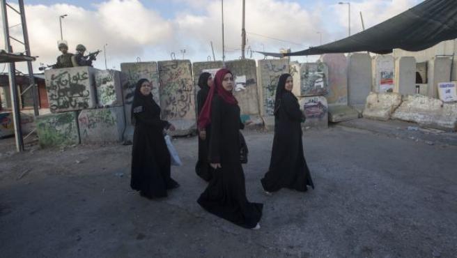 Mujeres palestinas cruzan la frontera desde Cisjordania a Jerusalén para asistir a las primeras oraciones del viernes del mes de Ramadán en la mezquita de Al-Aqsa a través del punto de control de Kalandia (Palestina).
