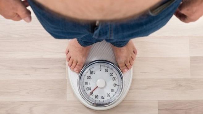 Un hombre comprueba su peso en una báscula de baño.