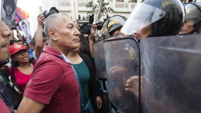 Manifestantes se enfrentan a la Policía, que impide el paso de una marcha en contra del indulto al expresidente de Perú Alberto Fujimori.