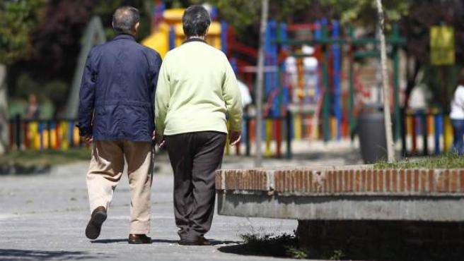 Dos jubilados pasean por un parque.