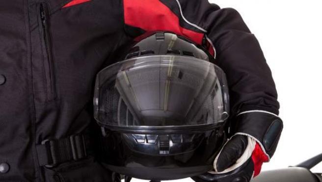 Un motorista sosteniendo el casco con vestimenta protectora.