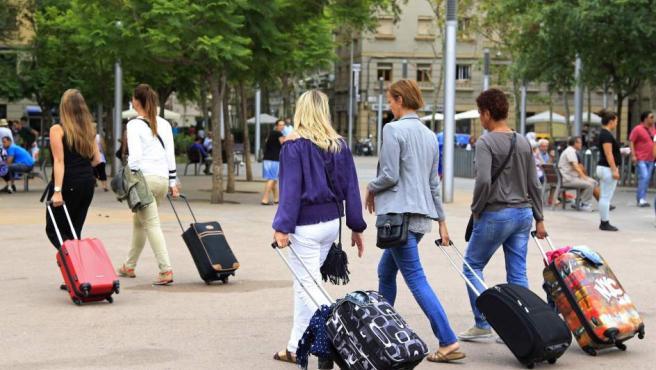 Unas turistas buscan su hospedaje en el barrio de la Barceloneta.