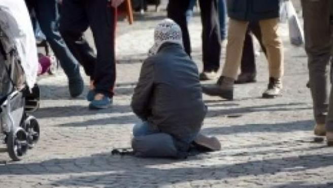 Un indigente pidiendo en la calle.