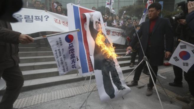 Un grupo de manifestantes quema una foto del líder norcoreano, Kim Jong-un, durante una protesta en Seúl contra la participación de Corea del Norte en los Juegos Olímpicos de Invierno.