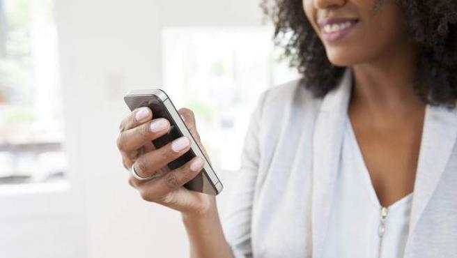Una mujer utilizando su teléfono móvil.