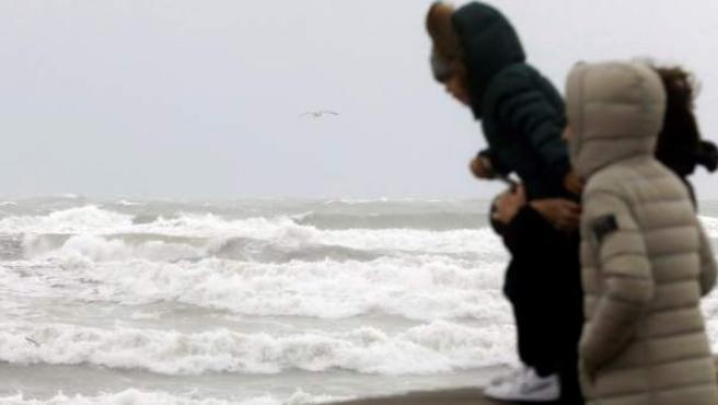 Tres personas observan el temporal marítimo en la playa de la Malvarrosa de Valencia