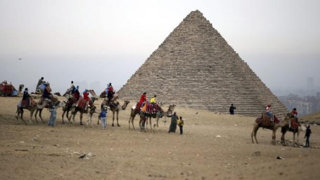 Varios turistas disfrutan de un paseo a camello delante de la Pirámides en Guiza (Egipto).
