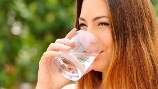 Una mujer bebe agua.