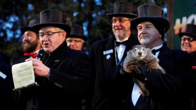 El cuidador John Grifiths (d), del Club de la Marmota, sostiene a la marmota Phil mientras el vicepresidente del club, Jeff Lundy (i), lee la predicción de Phil para este año en Punxsutawney, Pensilvania (EE UU). Según Phil aún quedan seis semanas más de invierno.