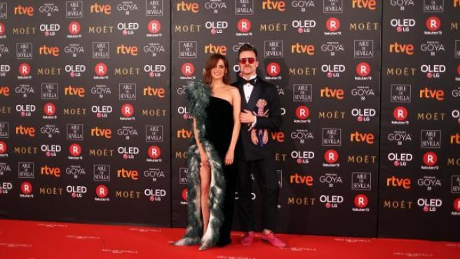 La actriz Macarena Gómez, vestida con un diseño de Teresa Helbig, y su pareja Aldo Comas, con un arriesgado esmoquin decorado con una langosta de pedrería, posan sobre la alfombra roja de los Goya 2018.