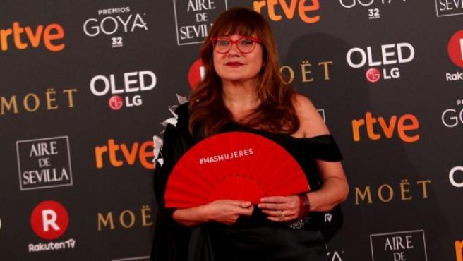 La directora Isabel Coixet posa sobre la alfombra roja de los Goya 2018, con un abanico en el que se puede leer el mensaje reivindicativo #Masmujeres.