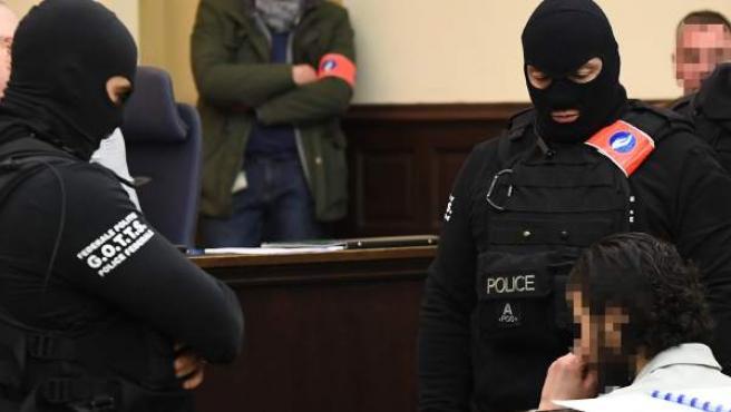 Agentes de policía enmascarados permanecen junto a Salah Abdeslam durante su juicio en Bruselas.