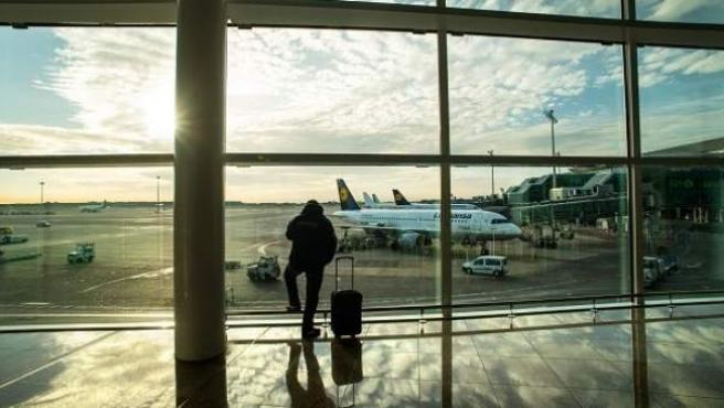 Viajero con maleta en aeropuerto.