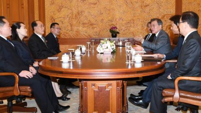 Representantes del Gobierno de Corea del Norte (izquierda), se reúnen con el presidente de Corea del Sur, Moon Jae-in (tercero por la derecha, alzando la mano) y otras cargos del país.