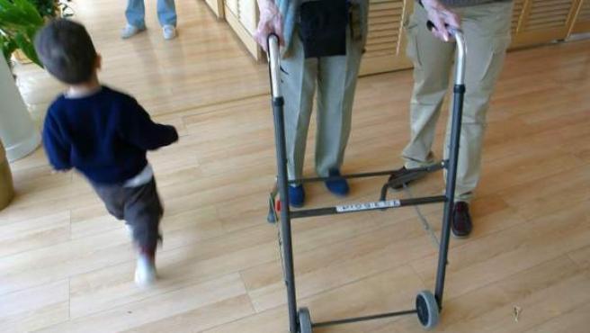 Un anciano con andador pasa junto a un niño, en una imagen de archivo.