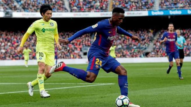 El delantero japonés del Getafe Gaku Shibasaki (i), y el defensa colombiano del Barcelona Yerri Mina, durante el partido de la vigésimo trecera jornada de LaLiga que se disputó en el Camp Nou en Barcelona.