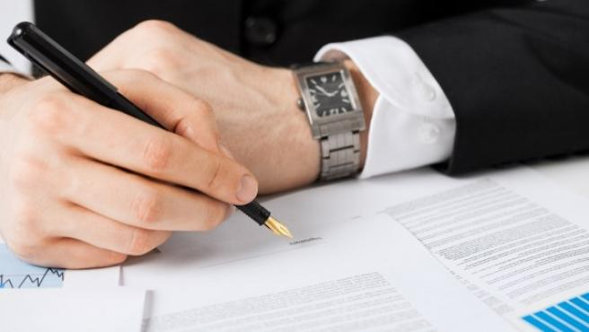 Un hombre firma un contrato en una oficina.