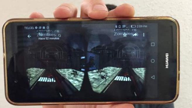 """Un joven muestra el videojuego para teléfonos móviles en el que el jugador debe disparar y matar a """"pejezombies"""", simpatizantes del líder izquierdista López Obrador."""
