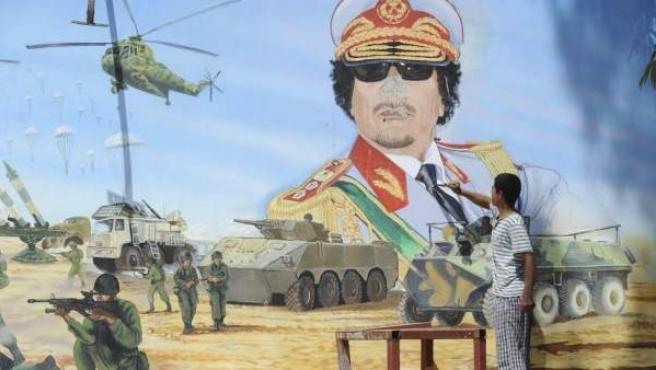 Un joven utiliza un objeto punzante para destruir una pintura mural que representa al dictador libio Muamar el Gadafi, muerto en octubre de 2011.