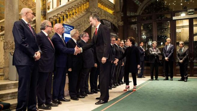 El rey Felipe VI saluda al consejero delegado de la asociación GSMA, John Hoffman (3-i), entre otras autoridades, antes de presidir la cena de bienvenida del Mobile World Congress.