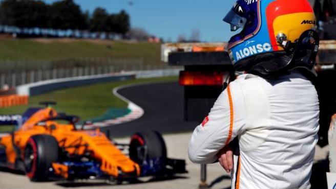Fernando Alonso contempla su McLaren averiado en Montmeló.