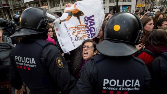 Efectivos de los Mossos d'Esquadra desalojan a un grupo de mujeres que cortaban la Gran Via de Barcelona, durante la huelga feminista del 8-M.