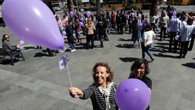 Un grupo de hombres y mujeres regalan a los viandantes de la zona de Triana, en Las Palmas de Gran Canaria, globos morados con motivo del Día Internacional de la Mujer.