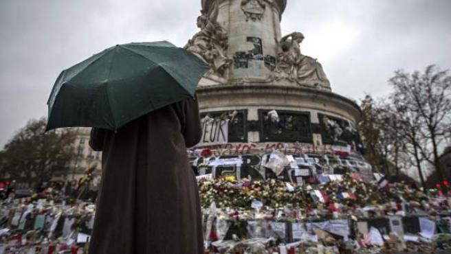 Una persona permanece frente al santuario improvisado en homenaje a las víctimas de los atentados perpetrados por el Estado Islámico (EI) el pasado 13 de noviembre, en la plaza de la República de París (2015).