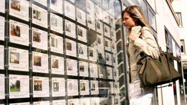 Una mujer observa las ofertas de pisos en el escaparate de una inmobiliaria.