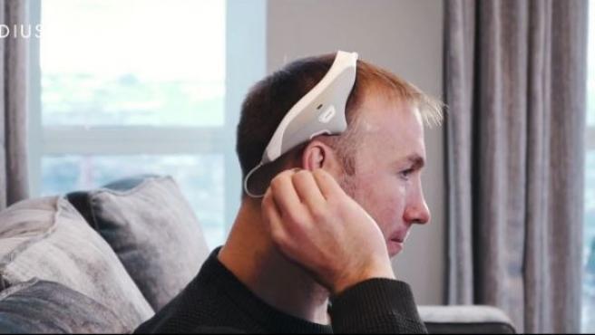 Imagen promocional de un hombre colocándose los auriculares Modius.