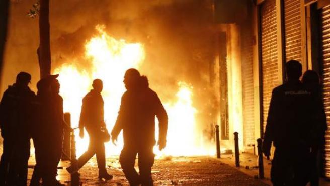 Contenedores incendiados en la calle Mesón de Paredes con la calle del Oso, en el barrio de Lavapiés.