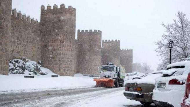 Una máquina quitanieves trabaja para retirar la nieve caída junto a la muralla de Ávila.