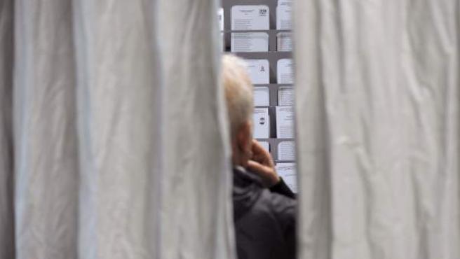 Un hombre, en el interior de un colegio electoral de Pamplona, observa las papeletas electorales antes de votar, en el marco de las elecciones europeas.